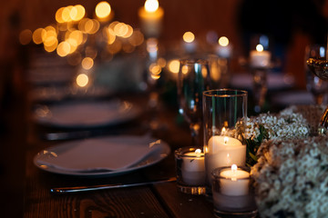 Candles on wedding table set on a beautiful lit background. Forget-me-not flowers lit by candles on wooden table