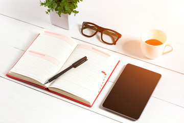 Office table desk with set of supplies, white blank notepad, cup, pen, tablet, glasses, flower on white background. Top view