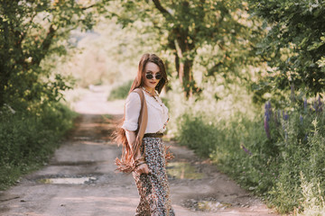 A portrait of young beautiful brown hair hippie girl walking path in park wearing bo-ho clothes and sunglasses looking back. Outdoors