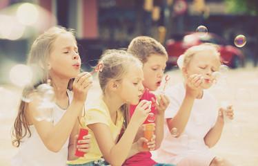 children blowing bubbles outdoors.