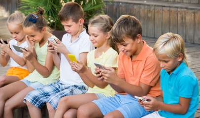 Group of cheerful kids playing with mobile phones outdoors