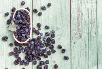 Ripe blackberries and blueberry in basket on rustic wooden table.