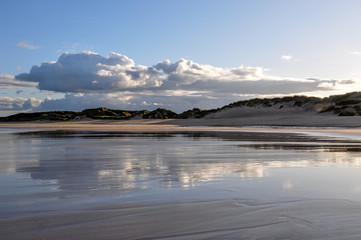 Clouds and Sand Dunes Reflecting on Wet Sandy Beach