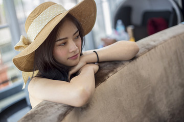 Adorable young asian girl arms crossed on couch with straw hat and wondering and thinking.  Copy space.