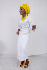 an African lady with head tie, bead necklace, beautiful makeup and smiling and dancing