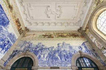 PORTO, PORTUGAL - JUNE 24, 2017: Ancient vintage Azulejos panel on inside walls of main hall of Sao Bento Railway Station in Porto city.