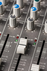 Audio mixing console with sliders and knobs on the channels.