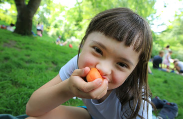 Young girl eating apricot in the park