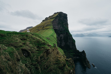 Lighthouse standing above jagged cliffs
