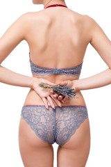 Slim, beautiful woman in lace lingerie holding bouquet of dry lavender isolated on white background. Free space for text.