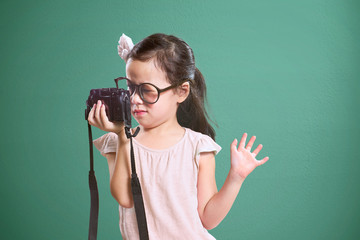 Little asian cute girl selfie with retro camera .  Vintage mint green wall background.