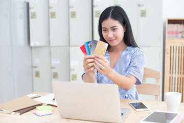 Beautiful asian women holding a lot of craditcard for shopping online with laptop, online shopping protrait concept.