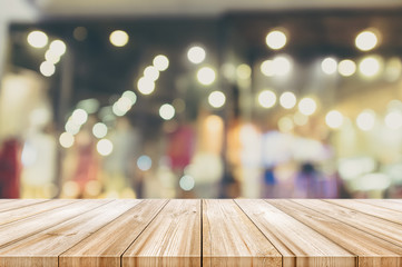 Empty wooden table top with blurred modern shopping mall background. Vintage color tone.