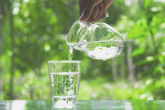Female hand pouring water from pitcher to glass on nature background