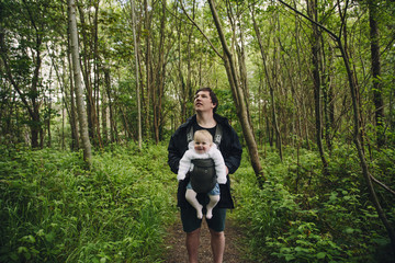 Father out for a walk in the forest with his baby girl in a baby carrier.