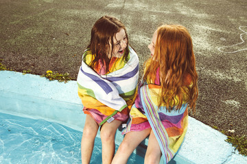 Two girls talking by pool with wet hair.