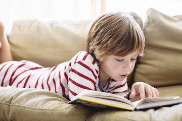 A young boy learns to read by himself in his pajamas on the sofa.