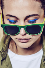 Portrait of a beautiful teenage girl with sunglasses and blue eye make up.