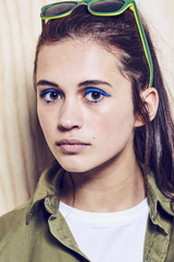 Head shot of a beautiful teenage girl with blue eye make up.