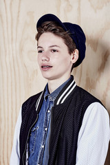 Teenage boy with black cap and  braces poses for mid length portrait against plywood.