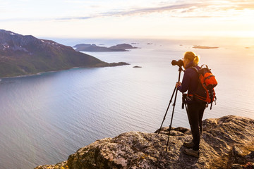 Woman photographer photographing fjord in Norway with DSLR and tripod