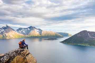 Woman hiker looking at a beautiful Norwegian Fjord landscape