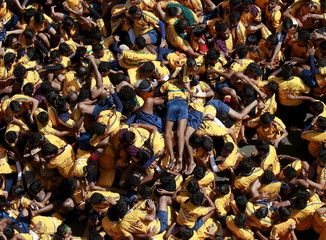 Devotees tumble as they try to form a human pyramid to break a clay pot containing curd during Janmashtami celebrations in Mumbai