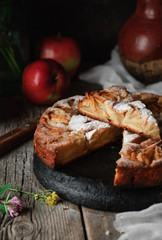 Homemade rustic Italian apple pie, a mug of milk, a pot of chamomile flowers, two raw fresh apples, a jug and meadow flowers on a wooden old vintage table. Dark background. Seasonal bakery concept.