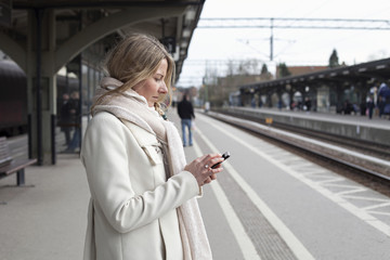 Woman waiting for train while looking at her phone