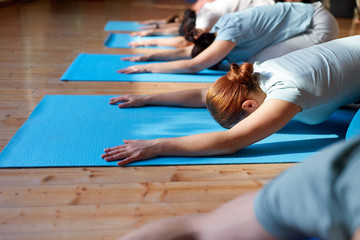 group of people doing yoga hare pose at studio