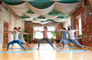 group of people doing yoga warrior pose at studio