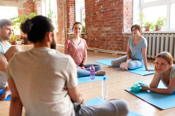 group of people resting on yoga mats at studio