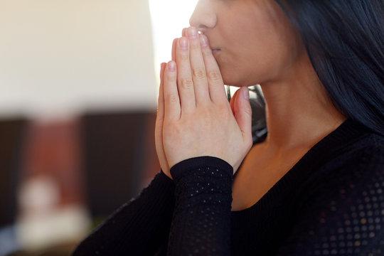 close up of sad woman praying god in church