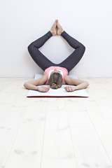 Woman in yin yoga butterfly pose, legs up the wall