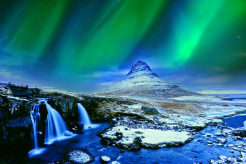 View of the northern light at dusk over Kirkjufell Mountain in Iceland.