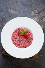 Risotto with strawberries served in a white plate, high angle view over brown stone surface, vertical shot