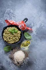 Risotto with spinach in a frying pan and cooking ingredients, high angle view over grey stone background with space, vertical shot