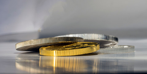 Gold and silver coins in close up on a blurred grey background. Selective focus.
