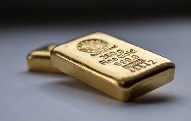 Two cast gold bars on a grey background. Selective focus.