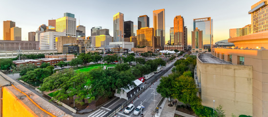 Aerial view downtown Houston illuminated at sunset with green city park and modern skylines light. The most populous city in Texas, fourth-most in United States. Architecture and travel background.