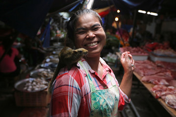 A woman walks with a squirrel on her shoulder at Maeklong market at the outskirts of Bangkok