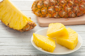 slice of pineapple in white plate on wooden table