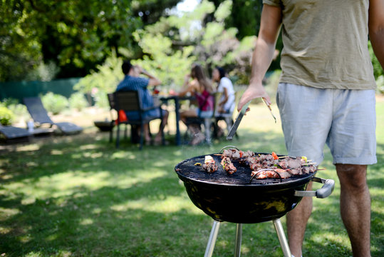 close up of a barbecue grill with meat and sausages cooking during summer garden party with people in background