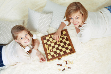Mother and child are playing chess while spending time together at home