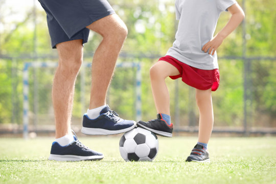 Legs of father and son with ball on soccer pitch