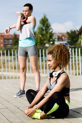 Two fit and sporty young women doing stretching in the park.
