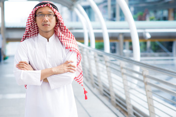 Confident arabian man with arms crossed with city in background