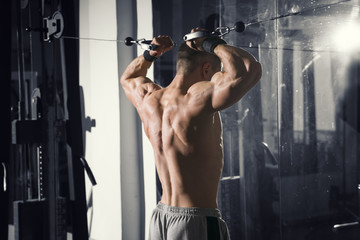 Bodybuilder workout on trainer in gym, perfect muscular male body