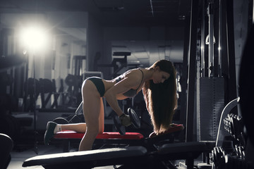 Young sexy fitness girl workout with dumbbells in the gym, woman with perfect muscular body