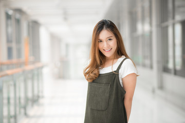 Portrait of beautiful young happy confident Asian woman smiling indoor